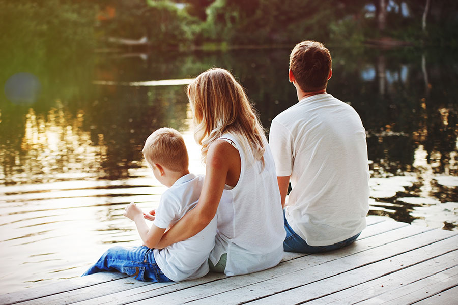 Blog - Young Family Sitting On Dock Looking Out At Lake