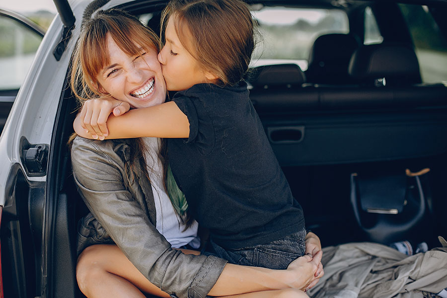 Personal Insurance - Happy Mother And Daughter Sitting In Back Trunk And Hugging